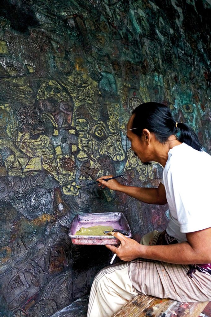 Celebrated Balinese painter I Made Djirna working in his home studio